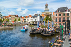 Rhine canal with cafes and church tower, Leiden, Netherlands Stock Images