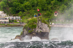 Rhine Falls in Neuhausen am Rheinfall, Schaffhausen, Switzerland. Neuhausen am Rheinfall, Switzerland - May 24, 2016: Tourists on a rock above the Rhine Falls in Royalty Free Stock Photo