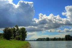 Rhine Landscape. A photo at Rhine, nice green grass, the Rhine and the blue sky full of clouds. Can be well used like wallpaper Stock Images