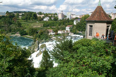 The Rhine waterfalls at Neuhausen on Switzerland. Neuhausen, Switzerland - 26 August 2008: People enjoying the view at the top of the rock that stands in the Stock Image