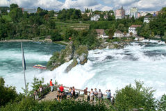 The Rhine waterfalls at Neuhausen on Switzerland. Neuhausen, Switzerland - 26 August 2008: People enjoying the view at the top of the rock that stands in the Royalty Free Stock Photography