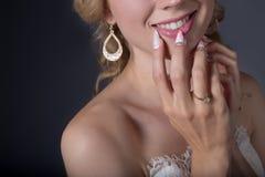 Όμορφη νύφη κοριτσιών χεριών στο άσπρο γαμήλιο φόρεμα με τα ακρυλικά καρφιά και το λεπτό σχέδιο και rhinestones Στοκ φωτογραφία με δικαίωμα ελεύθερης χρήσης