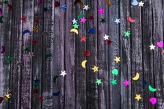 Rhinestones on wooden background. Wooden background. Sequins of different shapes. Sequins for manicure and pedicure. Sky with stars royalty free stock photos