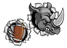 Rhino American Football Ball Breaking Background. A rhino angry animal sports mascot holding an American football ball and breaking through the background with Stock Image
