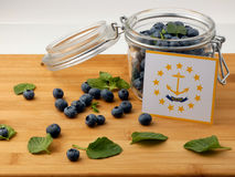Rhode Island flag on a wooden plank with blueberries  on Stock Photos