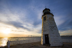 Rhode Island: Goat Island Lighthouse. Sunset over the Goat Island Lighthouse, Newport, RI with Claiborne Pell Bridge and Rose Island Light House as a backdrop stock images