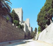 Rhodes castle view of walls battlements and towers taken from the dry moat with blue sky Stock Photos