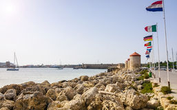 Rhodes city coast with ancient windmills and flags Royalty Free Stock Image