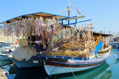 Souvenir shop organized on traditional Greek wooden boat at port of Rhodes town. Royalty Free Stock Photos