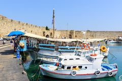 Traditional Greek fishing boats are staying moored at sea port of Rhodes town on Rhodes island, Greece Stock Photos