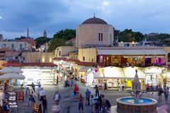 People on Hippocrates Square in Rhodes, Greece. Rhodes, Greece - October 7, 2017: People walking and resting on Hippocrates Square in evening. Hippocrates Square Royalty Free Stock Photo