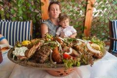 Rhodes Grekland Maj 30, 2018 Meze platta med traditionell lokal mat på tabellen i lokal restaurang framme av en familj Gammal sta arkivfoton
