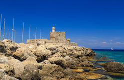 Rhodes harbor with the old fort in the background and stones in the foreground Royalty Free Stock Photos