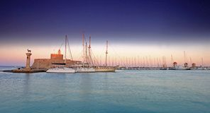 Rhodes harbor and windmills in Greece at sunset Stock Image