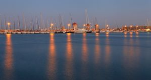 Rhodes harbor and windmills in Greece at sunset Stock Photo