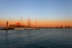 Rhodes harbor and windmills in Greece at sunset Royalty Free Stock Photography
