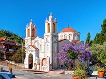 RHODES ISLAND, GREECE, JUN 22, 2015: Traditional beige orange colors Greek church Agiou Panteleimonos among green hills violet tre. Es, red flowers. Famous Stock Photos