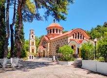 RHODES ISLAND, GREECE, JUN 28, 2015: Traditional Greek church monastery Saint Nektarios with bell tower among green trees. Famous stock photo