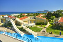 RHODES ISLAND, GREECE, JUN 22, 2013: View of Grecotel Rhodos Royal villas, swimming pool water slides, tourists. Traditional Greek royalty free stock images