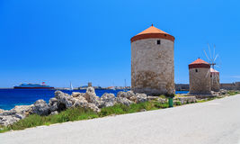 Rhodes mills on the background of the sea bay and the port sunny day Royalty Free Stock Photography