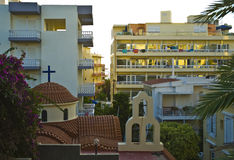 Rhodes town. A tiny view to the sea through hotel buildings and over a small greek church in Rhodes stock photos