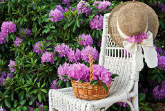 hat on wicker chair in rhododendron garden Stock Photos