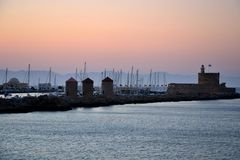 Rhodos老镇,当桃红色日落、风平浪静、希腊纪念碑和港口视图时 温暖的颜色,有雾的背景 Rhodos,希腊, E 免版税库存图片