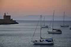 Rhodos老镇,当桃红色日落、风平浪静、希腊纪念碑和港口视图时 温暖的颜色,有雾的背景 Rhodos,希腊, E 免版税库存照片