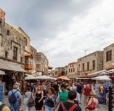 RHODOS, GRECIA 14 DE JUNIO DE 2016: Muchos turistas que visitan y que hacen compras en la calle de mercado en la ciudad vieja Rho Fotografía de archivo