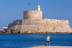 Rhodos, Greece - August 2016: Fort of Saint Nicholas at the entrance in the Mandraki old harbour of the City of Rhodes. Dodecanese islands are famous tourist royalty free stock photography