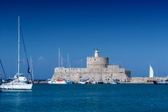 Rhodos, Greece - August 2016: Fort of Saint Nicholas at the entrance in the Mandraki old harbour of the City of Rhodes. Stone fortress or castle on the royalty free stock photography