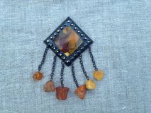 Vintage Amber brooch. Rhomb shaped Russian vintage amber brooch on linen background Royalty Free Stock Photos