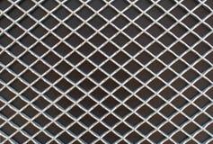 Rhombus metal pattern on black surface. Photograph of rhombus metal grid pattern on black surface Royalty Free Stock Photo