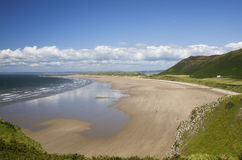 Rhossili Bay, Gower, Wales. View of Rhossili Bay with hills and cloudy blue sky Royalty Free Stock Image