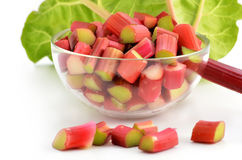 Rhubarb. Fresh cut up rhubarb in glass dish with stalk and leaf behind Stock Photos