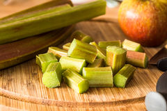 Rhubarb and Apple on Wooden Board. Chopping Rhubarb on a wooden  board with an Apple in the background and sticks of Rhubarb placed on the side ready to be Royalty Free Stock Photos