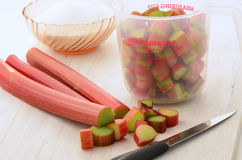 Rhubarb for jam. Rhubarb being prepared to make jam with two cups of cut rhubarb and bowl of sugar Stock Photo