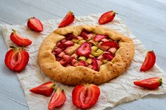 Rhubarb tart with strawberry on the gray concrete background. Vegetarian healthy rhubarb galette decorated with fresh strawberries. Rhubarb tart with strawberry Royalty Free Stock Photo