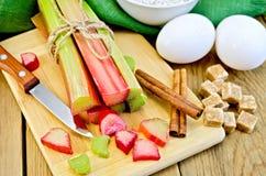 Rhubarbe avec du sucre et des oeufs sur le conseil Photos stock