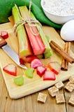 Rhubarbe avec du sucre et le couteau à bord Images stock