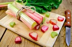 Rhubarbe coupée à bord avec le couteau Photos stock