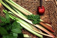 Rhubarbe dans le panier avec le baume et l'Apple de citron Image libre de droits