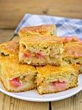 Rhubarbe de tarte dans le plat et la serviette à bord Images stock