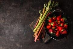 Rhubarbe et fraises sur la table de cuisine rustique foncée Copiez l'espace Aliment biologique saisonnier Consommation et cuisson photo libre de droits