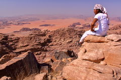RHUM DE WADI, JORDANIE - 12 NOVEMBRE 2010 : Un homme jordanien donnant sur le désert de Wadi Rum du haut d'une montagne Photos libres de droits