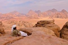 RHUM DE WADI, JORDANIE - 12 NOVEMBRE 2010 : Un homme jordanien donnant sur le désert de Wadi Rum du haut d'une montagne Photo libre de droits