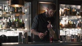 Rhum se renversant de barman barbu professionnel dans le becher en métal, puis en verre Barman faisant le cocktail dans la barre  clips vidéos