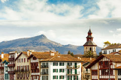 The Rhune Mountain. View of the famous Rhune mountain, at the foreground, the Ciboure harbor's bells tower and some typical bask buildings Royalty Free Stock Images