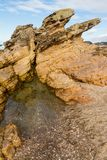 Wave eroded rhyolite lava formation on the shoreline. This rhyolite lava flow has been eroded by centuries of exposure to the tide and now shelters a rock pool royalty free stock photography
