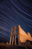 Rhyolite at Night. Star trails above the ruins of Cook bank Stock Photos